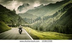 Motorcyclist on mountainous highway, cold overcast weather, Europe, Austria, Alps, extreme sport, active lifestyle, adventure touring concep...