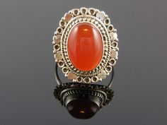 Made with 10x14mm oval carnelian agate cabochon gemstone and sterling silver wire. Size 7.75