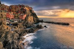 The Cinque Terre, famous worldwide for their five enchanted medieval villages with small fishermen ports, narrow cobblestone lanes and romantic trails, are also a gold mine of landscape photography opportunities.And Manarola, with its colourful fishermen's houses clinging onto the rugged cliffs and its tiny port, is probably the most pictoresque among the five villages. I took this picture on a  evening of January, at the end of a rainy and windy day. The wind was calming down after the…