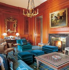 Neo-classical mahogany-paneled library-den features a Regency gilt-bronze chandelier, antique Venetian mirror, gorgeous teal velvet upholstery, and an inlaid low table by designer John Stefanidis.