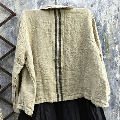 "This jacket is the newest ""must have"" item in your wardrobe. A heavy natural linen featuring black stripes on the back, it comes in two sizes and is designed to be worn oversized. The relaxed fit of the sleeves allow it to be worn alone or over another piece. It is finished with gorgeous mother of pearl buttons and a s"
