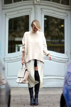 Oversize knit layered over a center slit dress with knee high black socks