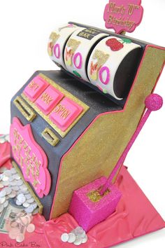 70th Birthday Slot Machine Cake!  Lots of glitter with bold gold and pink colors covers the slot machine.
