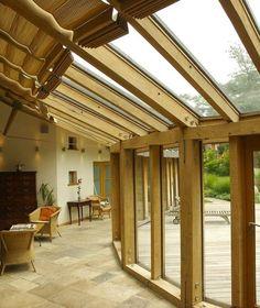 véranda bois qui suit la forme de la açade avec toiture vitrée et stores