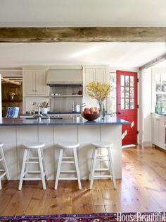 "Simple Shaker-style kitchen cabinets in a creamy color are set off by dark counters made of Vermont soapstone, ""a living material that will age and stain over the years, and that's part of its beauty,"" says Gourd."