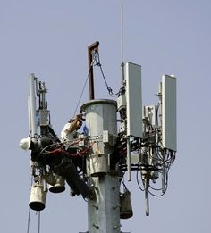 Two men working on a wireless cell tower.