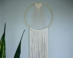 SHOP NOTICE: I am due to have my first baby in the first week of December! I will likely temporarily close my shop during that time, so get those holiday orders in soon! Dreamy handmade macrame wall hanging, made from 3mm natural white cotton rope and a 14 brass ring. Features a sleek modern design and long fringe. Choose between 60 and 75 total length. Shown here in 75 length. Would make a lovely gift! This item is MADE TO ORDER. Please allow 3-5 business days for production. ✦ 6 Ring…