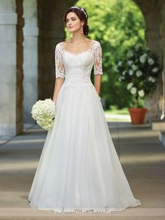 Organza full A-line gown with illusion lace three-quarter length sleeves and scoop neckline, sweetheart lace bodice with scalloped natural waist, illusion lace back with covered buttons, chapel train. Sizes: 0 – 20, 16W– 26W Colors: Ivory, White