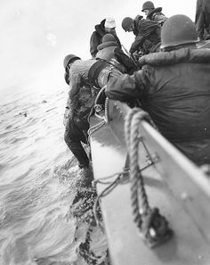 A survivor is pulled aboard a U.S. Coast Guard boat after his ship was hit during the Normandy landings, circa 6 June 1944.