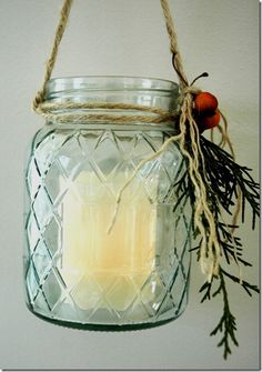 Simple candle holder out of pretty mason jar embellished with evergreen, holly berries & twine.