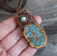 Walnut shell embedded with turquoise and then adorned with clay. This is beatiful