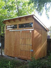 """Current shed has to be elevated 12-18""""; this is a nice shed; Garage with barn door & transom windows above door ... get this larger like a garage and have a little less pitch in roof, and in composite and it could be great"""
