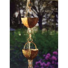 A fascinating alternative to the simple downspout. Rain chain catches rooftop water flow and creates its own watercourse, as water runs down the chain through a succession of 11 copper-coloured cups.