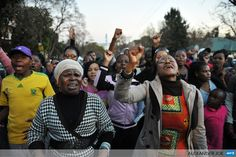SOUTH AFRICA, Pretoria : A group of Pretoria residents sing for former South African president Nelson Mandela outside the Mediclinic heart hospital in Pretoria on June25, 2013, where the former anti-apartheid leader spent a second night in critical condition in hospital with his family members, compatriots and well-wishers worldwide fearing he is about to lose his final struggle. AFP PHOTO / ALEXANDER JOE