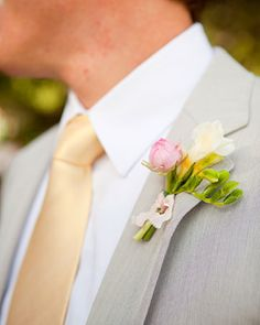 A peony bud and double white freesia adorned this groom's lapel for a spring wedding
