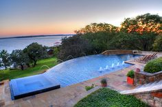 Infinity pool overlooking ocean at sunset. Water features include laminar fountains, perimeter overflow spa, and fountain bubblers | Westside Pools, Fort Worth, TX http://www.luxurypools.com/swimmingpoolbuilder/Westside-Watershapes?fid=202 Adam Wood Photography