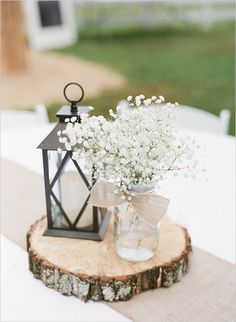 Elegant rustic wedding table centerpieces with a lantern & candle, decorated mason jars and lovely flowers