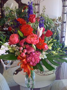 Floral arrangement with peonies, roses, lilies,delphiniums,and monestera leaves.