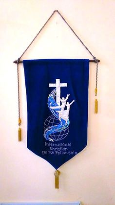 International Christian Dance Fellowship Banner made in Oamaru, New Zealand in 1991 for the 1st ICDF Conference in Jerusalem, Israel. It is in royal blue velvet with silver lamé cross and figures, blue sequinned satin river, with the world represented by corded globe.  This photo was taken at the ICDF Conference in Ghana by Belinda Andrews...