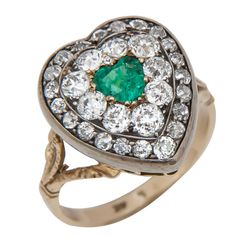 Circa 1910 Silver Topped and Gold Heart Shaped Ring, set with 2 Carats of Old Mine Cut Diamonds and centrally set with a Heart Shaped Emerald.