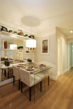 A parede da sala de jantar foi revestida com espelho lapidado e polido, com prateleiras em fórmica branca para comportar os adornos e também funcionar como aparador para a mesa de jantar. Essa, em vidro com cadeiras em suede cru e pés em madeira