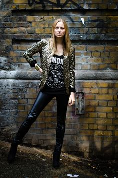 Sporting an 80s glam rock inspired outfit with a gold sequined blazer and vinyl leggings.