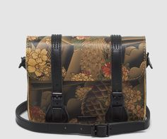 Our 7 Leather Satchel- the smallest of our classic satchel collection- gets updated in this season's Tattoo Sleeve print. Inspired by the iconology and styling of US Hardcore bands and their fans, this bag is sure to stand out in a crowd with its intricate print of Japanese-influenced tattoo art-- including koi fish, cherry blossoms, peacocks and clouds. Its shiny black hardware and triple stitch detailing on the straps and the back show off its quality detailing. With magnets placed ...