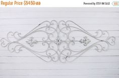 Large shabby chic iron wall decor with loads of swirls . Flower medallion in the middle with fleur de lis on each end..A perfect piece for any