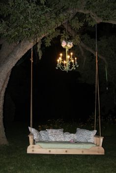 Chandelier and swing hanging from the tree.