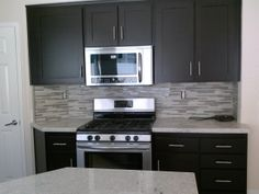 Glass and stone backsplash, quart countertop  and refinished cabinets transformed this kitchen to modern beautiful. Call us for your affordable remodel. ranchointeriordesign.com