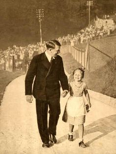 Hearing that a little girl in the crowd has the same birthday as him, Hitler fetches her up to the Berghof. She is Bernile Nienau.