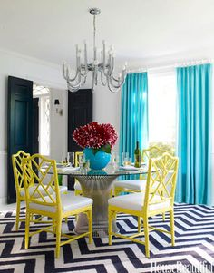 Black and White with Lemon and Turquoise. Could buy large black and white chevron rug to layer white rug over. Add solid turquoise curtains which will blend with painting. Then add black chest and zebra throw pillow and done.