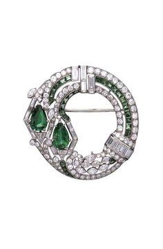 N ART DECO EMERALD AND DIAMOND BROOCH. Set with two pear-shaped emeralds, within a baguette-cut diamond surround, accented by trillion-cut diamonds, extending a circular openwork scroll, composed of old European, circular and single-cut diamonds and square-cut emeralds, enhanced by baguette-cut diamonds, terminating with marquise-cut diamond detail, mounted in platinum, circa 1925.