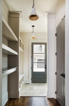 Gray beadboard doors open to the mudroom facing a wall of stacked shelves next to open lockers illuminated by white and gold pendants.