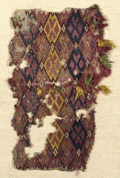 This textile is thought to have also been a bag face, since the fabric selvages can be seen on both sides. The fabric size is 11 x 19cm and is a weft woven linen with silks of pink, indigo, blue and yellow and brown. The decoration is lozenge shaped with associated tassels. Possibly 14th century, it was sold by Christie's for £3,750 (or $7,631).