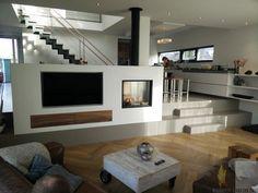 Moderne inbouw haard in een kolom met doorkijk, naast de ingebouwde televisie en ingebouwde lades met houtfront | Profires partner Reijnhoudt & van der Zwet · inspiratie voor sfeerverwarming