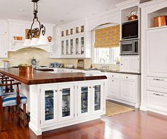 like white cabinets with butcher block island top to break it up