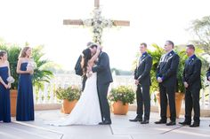 Bride and groom kiss in front of giant wooden cross decorated with flowers Mission Inn, Wedding Arches, First Kiss, Bridesmaid Dresses, Wedding Dresses, Hotel Wedding, Plaza, Wedding Hairstyles, Groom