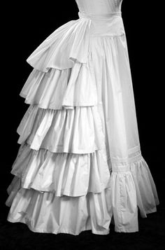 "The Bustle Petticoat is designed to be worn over the 19th Century Bustle. The front is smooth, slightly gathered into the short front yoke. The ruffled back smoothes the line of the bustle boning. It has a short sweep, is approximately 40"" long, and includes two tucks for altering the length."