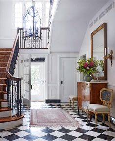 I love how they made the very formal chairs fun by the way they upholstered them; the black stone baseboards against the white walls, the the sweeping victorian staircase the checkered marble floor...