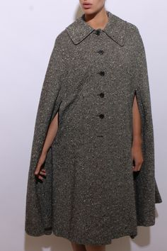This vintage 1970s cloak is made of nubby black and cream tweed, and features black leather trim on the arm openings.  #1970s #vintagecloak #btmvintage Shop now at: www.btmvintage.com