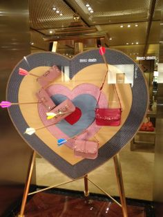 UNKNOWN | We love the idea of creating a heart shaped bullseye to display product hung from arrows.   This simple display would be easy to update & highlight different merchandise every day. #ValentinesDay #StoreDisplay #VisualMerchandising