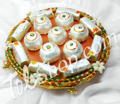 Rakhi Thaali A delicately designed rakhi thaali lined with orange tissue fabric and border of Mauli threads embellished with dainty mogra flowers. This pack contains: Kaju Roll - Made of puje kaju. Net weight: 125 grams. Kaju Lemon - Made of pure cashew nut with wrapping of silver warq. Net weight: 125 grams. Rs 749/- http://www.tajonline.com/rakhi-gifts/product/r2703/rakhi-thaali/?aff=pint2014/