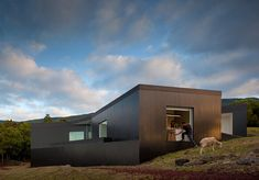 Portuguese studio SAMI Arquitectos completed a blackened timber house on the hillside of a Portuguese island.