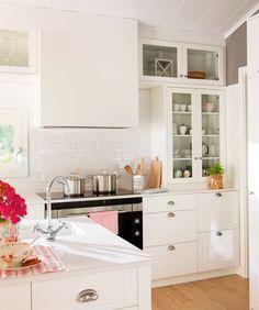 Con armarios hasta el techo: en esta cocina los metros se han exprimido al máximo. Para no recargarla en exceso, los módulos altos son tipo vitrina. Mobilirario, diseño de Carpintería Solé- Salas.