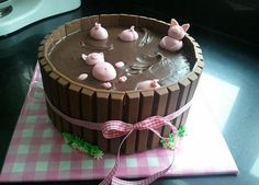 """Chocolate Cake Decorated as Pigs Floating in Mud: Kit Kat bar sides, fondant pigs, and chocolate ganache """"mud"""""""