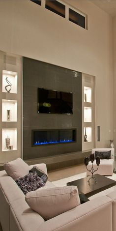 I like the wall fireplace and shelving! Sleek looking! The furniture is simple and comfortable. I also like the decorative piece on the table. More