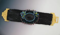 I made my old bead embroidery onyx cabochon pin and I embellished wired glass flower and leaf beads. I removed the pin to make a bracelet and used a black recycle bag for the base and I love the clasp.