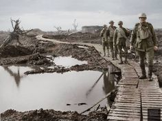 Four Australian soldiers at Chateau Wood near Retaliation Farm, walking over duckboards in the waterlogged fields to Zonnebeke, Flanders, Belgium. 22nd of October 1917.