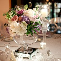 Soft-colored blooms and greenery were arranged in apothecary vases and placed atop mirrored risers.